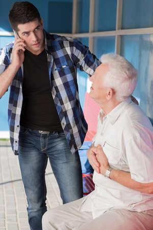 Young helpful man calling ambulance for elderly man