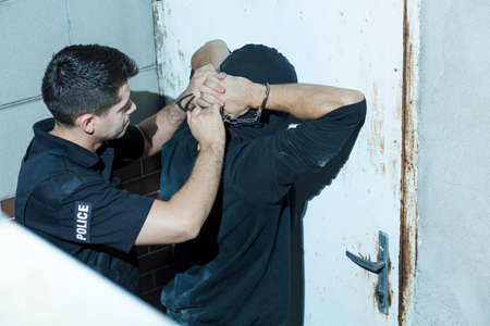 kidnapper: Horizontal photo of policeman overpowering masked kidnapper Stock Photo