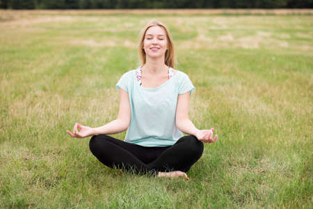 legs crossed: Girl with legs crossed practicing meditation on the meadow Stock Photo
