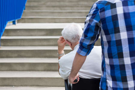 infirm: Senior man and dangerous city barriers for wheelchair