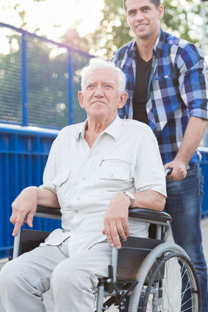 infirm: Smiling young man helping grandfather on wheelchair Stock Photo