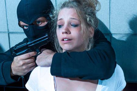 pointing gun: Masked man is pointing gun at girl Stock Photo