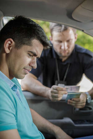 licence: Young policeman is looking at mans driving licence Stock Photo