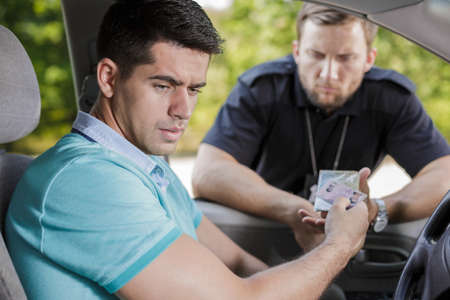 licence: Young driver is giving his driving licence to the cop