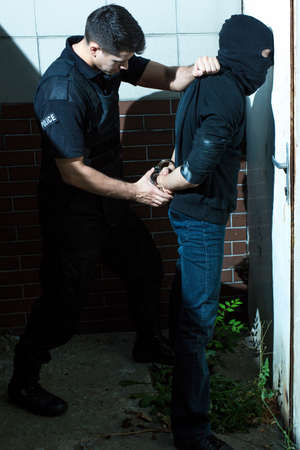 Photo of handcuffing wanted criminal by policeman Stock Photo