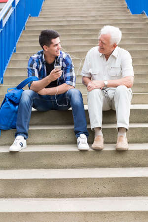pensionary: Young and elderly men are sitting on stairs Stock Photo
