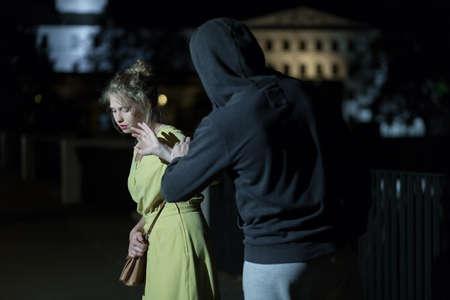 Gevaarlijke man en jonge vrouw op de straat Stockfoto