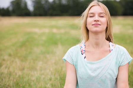 Fiatal nő csukott szemmel tapasztalható harmóniában a természettel