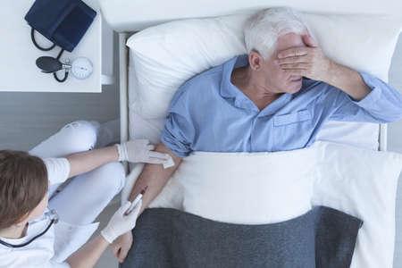 Shot van een arts die een injectie geeft aan haar patiënt