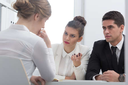 intern: Pretty professional boss asking a question to an intern Stock Photo