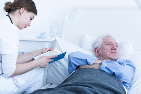 Shot of an angry senior man laying on a hospital bed and a nurse reading a book for him