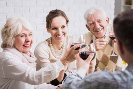 anecdote: Happy mature couple and young pair toasting, drinking red wine