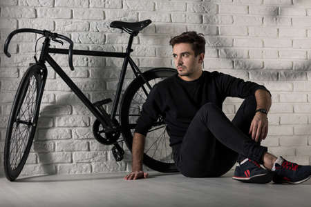 fashion style: Man sitting on floor next to a black bike, brick wall in the background