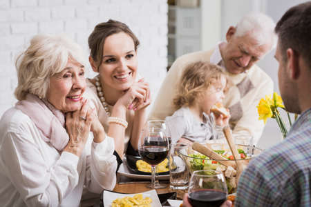 feier: Glückliche Familie neben Tisch beim Abendessen sitzen, Enkelin sitzen auf Großvater Schoß Lizenzfreie Bilder