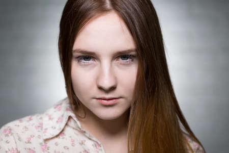 sadly: Shot of a young woman looking sadly at the camera
