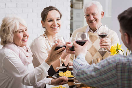 anecdote: Mature and young married couples toasting, sitting beside table, drinking red wine Stock Photo