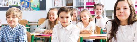 Panorama van een klaslokaal op de basisschool met rijen van lachende leerlingen zitten aan hun bureau