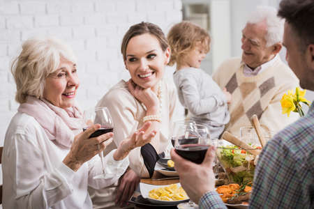 anecdote: Grandparents, granddaughter and young married couple sitting beside table during dinner