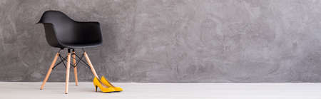 indoor background: Shot of a black chair and yellow high heels against grey wall Stock Photo