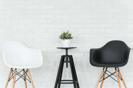 small table: Living room with two chairs and small table, decorative brick wall in the background Stock Photo