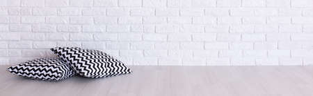 Shot of two black and white pillow laying on a floor