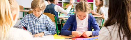 trabajo manual: Disparo de niños de escuela haciendo trabajos manuales en el aula, utilizando cartulinas de colores Foto de archivo