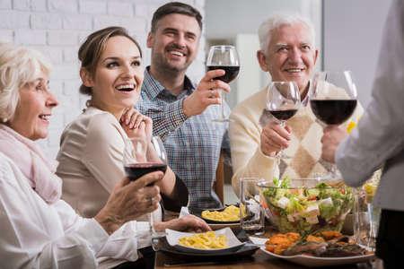 Glückliche Familie beim Abendessen, rösten, Gläser mit Rotwein Standard-Bild - 55595101