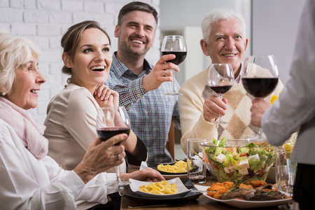 anecdote: Happy family during dinner, toasting, holding glasses with red wine