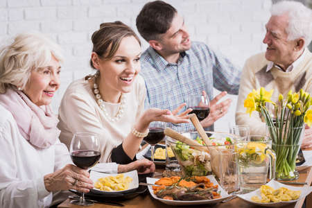 anecdote: Happy people during family, sunday dinner talking, smiling, drinking red wine
