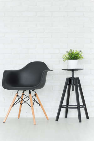 Black chair and small table, decorative brick wall in the background Stock Photo