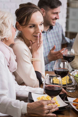 anecdote: Mature woman whispering to young woman, sitting beside table during family dinner Stock Photo
