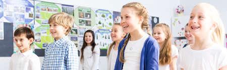 niños sonriendo: Panorama de los niños de escuela sonriente que se coloca en el aula