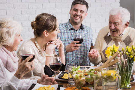 beside table: Happy family sitting beside table during dinner, smiling Stock Photo