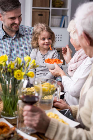 anecdote: Happy family eating together, grandmother feeding her granddaughter