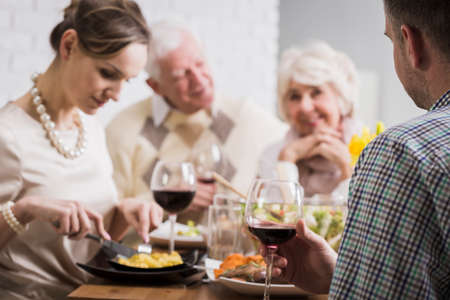 beside table: Mature couple and young marriage sitting beside table during family dinner