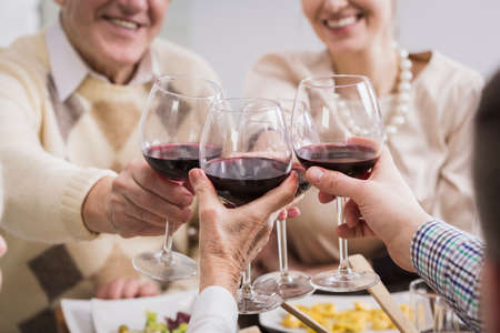 anecdote: Happy family toasting, holding glasses with wine, smiling