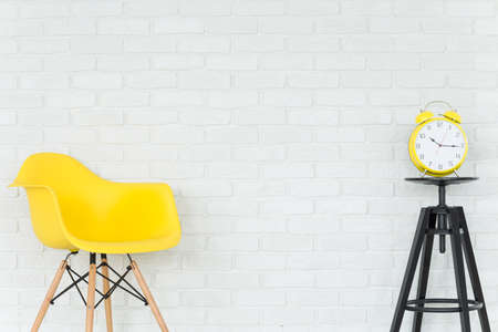 small table: Light interior with yellow chair, small table and trendy alarm clock, brick wall in the background