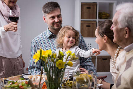 beside table: Happy family celebrating mothers day, sitting beside table during dinner Stock Photo