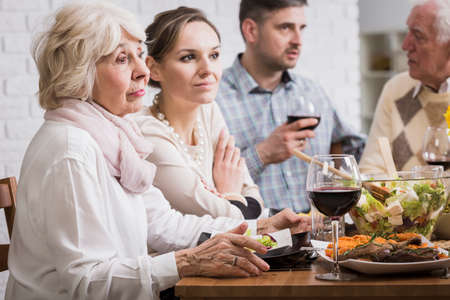 beside table: Two women and two men sitting beside table during family dinner, talking