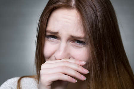 devastated: Portrait of a young woman crying and covering her face