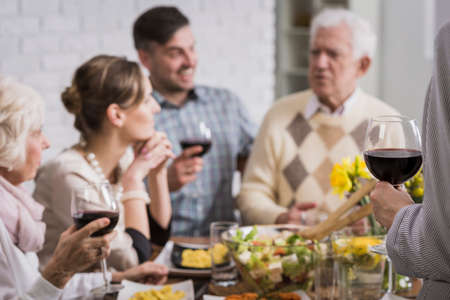 beside table: Happy family sitting beside table during meal, drinking wine