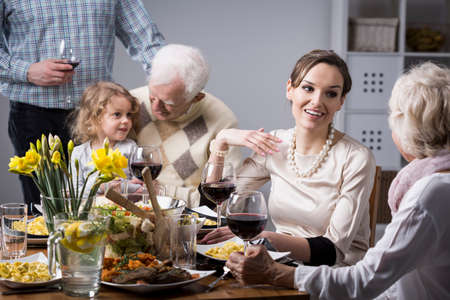 anecdote: Happy people during family dinner, talking and smiling Stock Photo