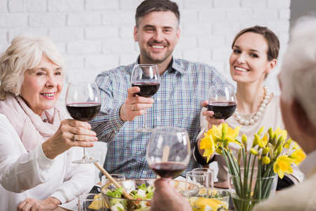 anecdote: Family drinking toast for elderly man, holding glasses with red wine, smiling