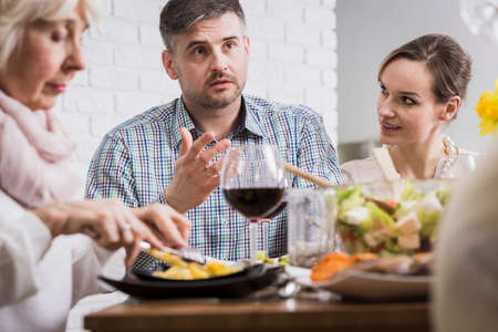 beside table: Young man and two women sitting beside table during family dinner