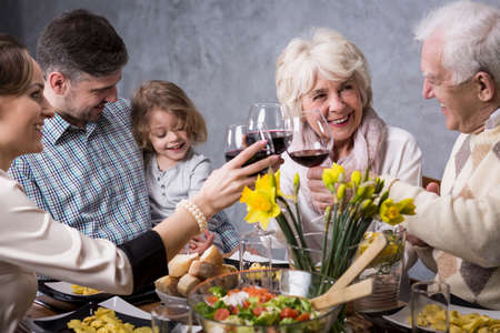 anecdote: Happy family during holiday dinner, smiling, talking, drinking red wine