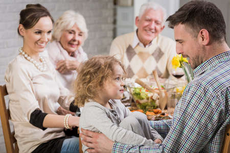 anecdote: Happy family during dinner celebrating fathers day, smiling