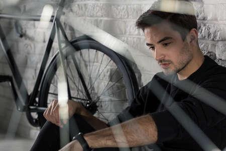 homme triste: Homme triste assis sur le plancher à côté de la bicyclette, mur de briques en arrière-plan