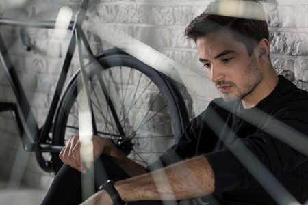 man sad: Sad man sitting on floor next to bicycle, brick wall in the background