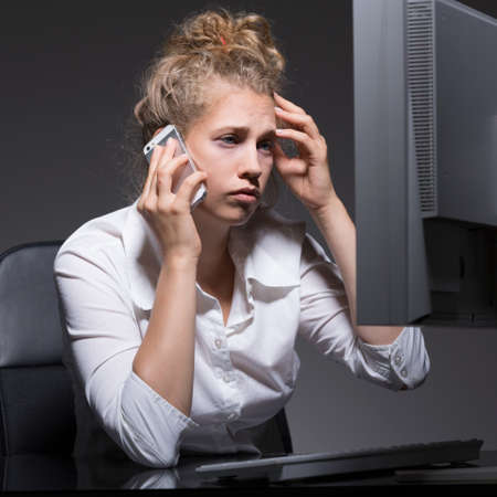 overtime: Tired office worker working overtime in corporation Stock Photo