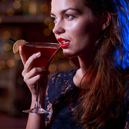alluring: Alluring woman in black dress drinking cocktail